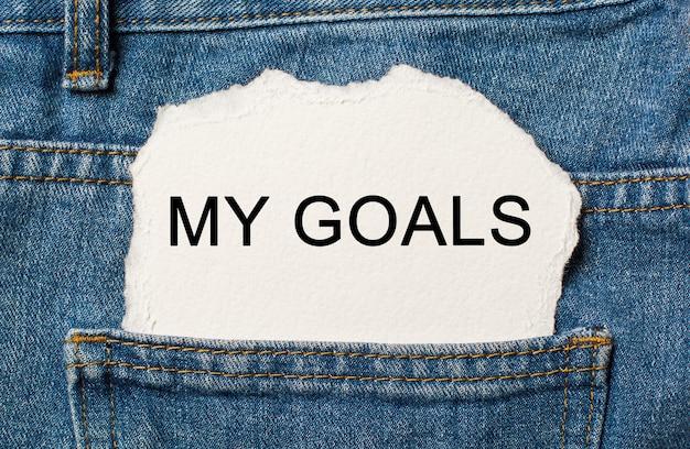 Moje cele na rozdartym tle papieru na koncepcji dżinsów i finansów