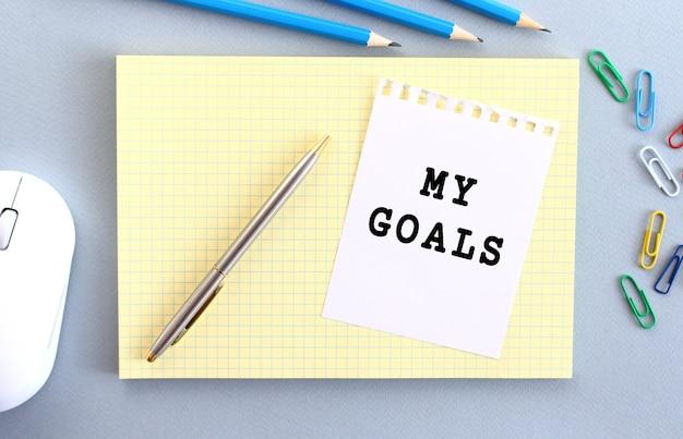 Moje cele są zapisane na kartce papieru, która leży na zeszycie obok materiałów biurowych. pomysł na biznes.