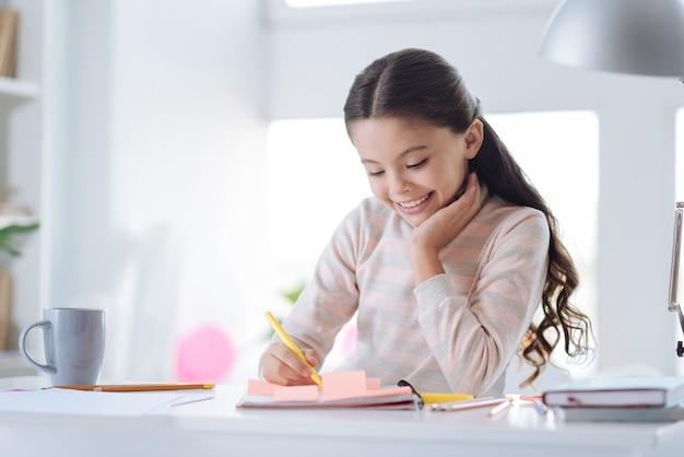 Moje domowe zadanie. zachwycona pozytywna wesoła dziewczyna siedząca przy stole i wykonująca swoje domowe zadania siedząc w swoim pokoju