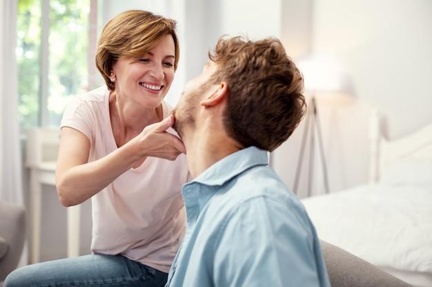 Moje dziecko. szczęśliwa starsza kobieta, patrząc na syna, dotykając jego brody