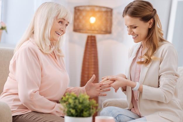 Moje gratulacje. miła radosna starsza kobieta uśmiecha się i patrzy na córkę, gratulując jej zaręczyn