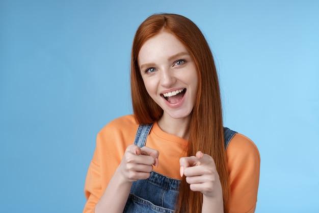 Moje gratulacje. sassy pewny siebie entuzjastyczny młoda atrakcyjna ruda dziewczyna z niebieskimi oczami wskazujący palec pistolety aparat uśmiechający się szeroko wiwatujący przyjaciel wykonał świetną robotę, gratuluję niesamowitej wydajności.