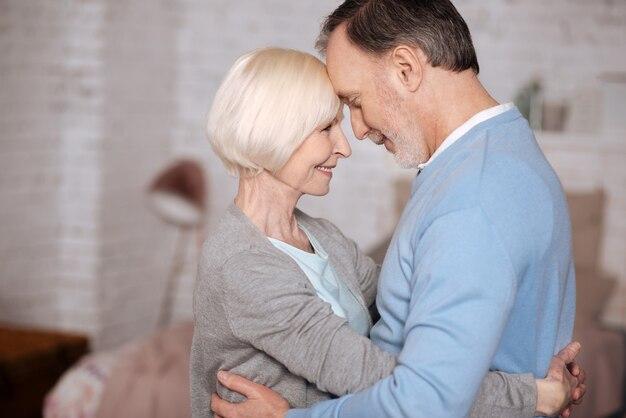 Moje kochanie. portret starsza para obejmując i patrząc na siebie, stojąc blisko w domu.