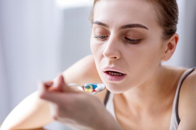 Moje lekarstwo. beztroska młoda kobieta trzyma łyżkę podczas jedzenia tabletek