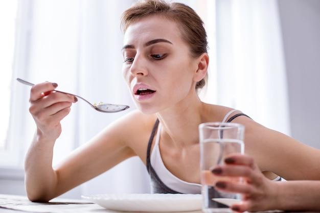 Moje lekarstwo. miła, bezradna kobieta trzyma szklankę wody podczas przyjmowania leków