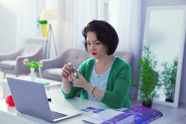 Moje miejsce pracy. ładny, dobrze wyglądająca kobieta siedzi przy laptopie podczas pracy