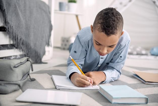 Moje myśli. skoncentrowany afro-amerykański chłopak leżący na podłodze podczas pisania w zeszycie