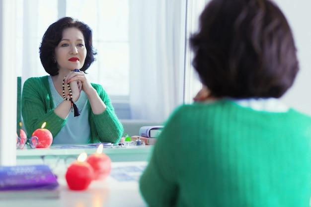 Moje odbicie. miła pozytywna kobieta siedzi przed lustrem, patrząc na swoje odbicie