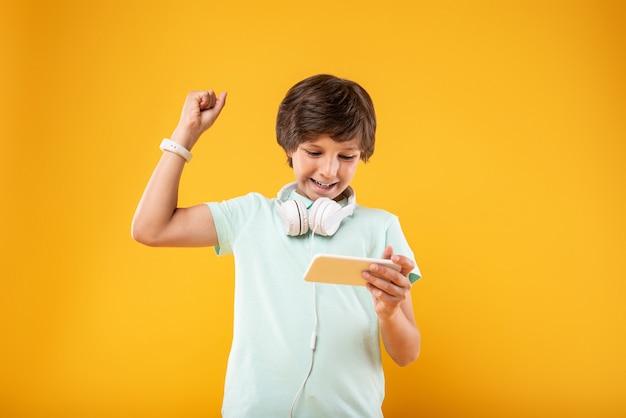 Moje podekscytowanie. przytłoczony ciemnowłosy uczeń korzystający z telefonu i noszący słuchawki