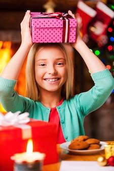 Moje prezenty świąteczne! śliczna dziewczynka niosąca pudełko na głowie i uśmiechnięta siedząc przy stole z choinką i kominkiem w tle
