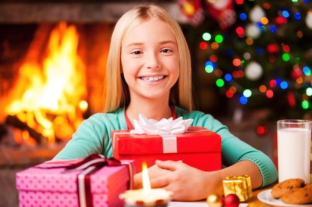 Moje prezenty świąteczne! śliczna dziewczynka obejmuje pudełko prezentów i uśmiecha się siedząc przy stole z choinką i kominkiem w tle