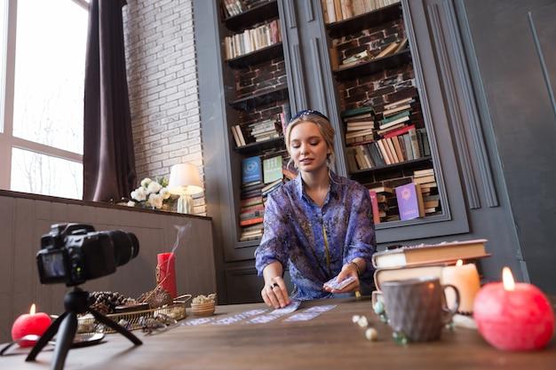Moje przeznaczenie. piękna młoda kobieta kładzie karty tarota na stole, chcąc zobaczyć swoje przeznaczenie