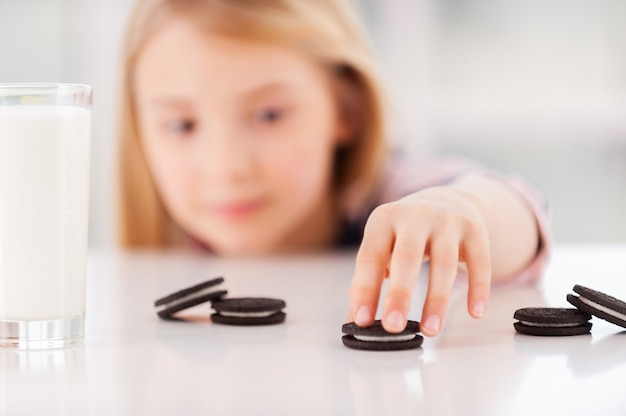 Moje ulubione ciasteczka! śliczna mała dziewczynka patrząca ze stołu i biorąca ciasteczka leżące na stole
