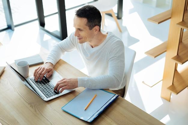 Moje ulubione zajęcie. radosny pozytywny miły człowiek siedzi przy stole i pracuje na laptopie, ciesząc się swoim zajęciem