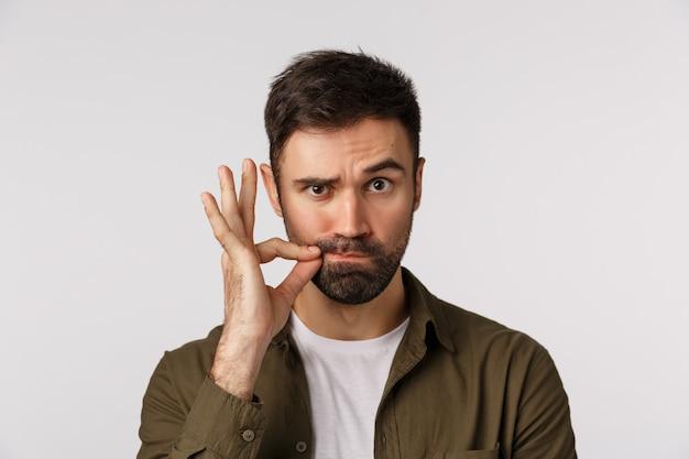 Moje usta są zapieczętowane obietnicą. poważny i zabawny brodaty dorosły mężczyzna nie odzywa się, wykonując gest zip i unosząc jedną brew, gdy osoba wskazująca milczy, zachowaj sekret