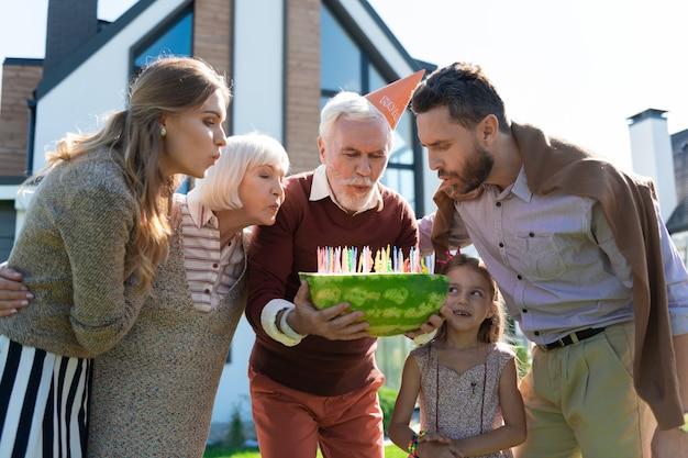 Moje wsparcie. radosny brodaty emeryt w papierowym kapeluszu i dmucha świeczki