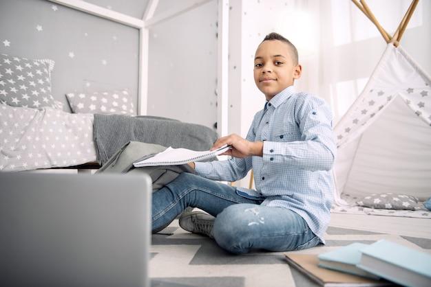Moje zadanie domowe. przyjemny afroamerykański chłopiec siedzi na podłodze, trzymając zeszyt z tornistra