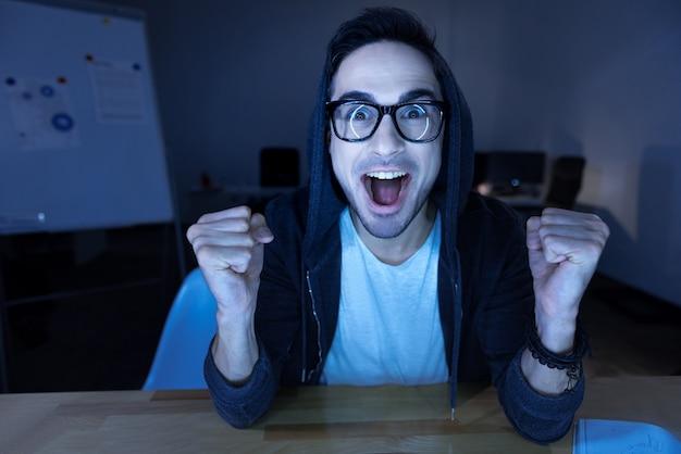 Moje zwycięstwo. szczęśliwy, radosny, emocjonalny człowiek, patrząc na ekran komputera i wyrażający swoje szczęście, wygrywając grę