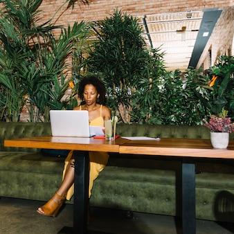 Mojito koktajl na drewnianym stole z młodą kobietą pracuje przy laptopem