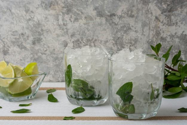 Mojito podane w kryształowym kieliszku z plastrami cytryny i listkami mięty na białym stole