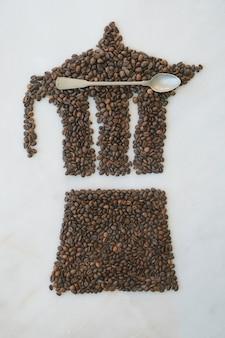 Moka pot ze świeżo palonych ziaren kawy na marmurowym tle z łyżeczką. wzór kawy.