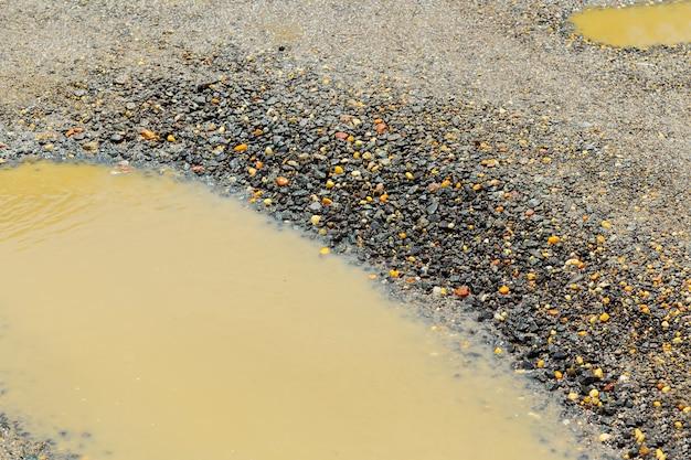 , mokra brązowa gleba w brudnej wiejskiej drodze po deszczu