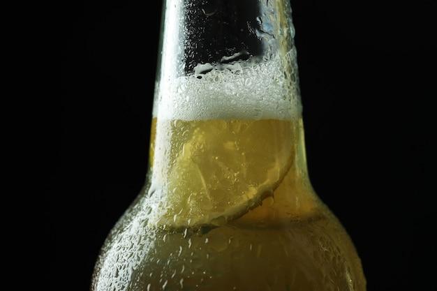 Mokra butelka piwa z wapnem na czarno, z bliska