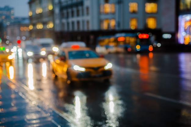 Mokra noc miasto ulica deszcz bokeh odbicie jasne kolorowe światła kałuże chodnik samochód