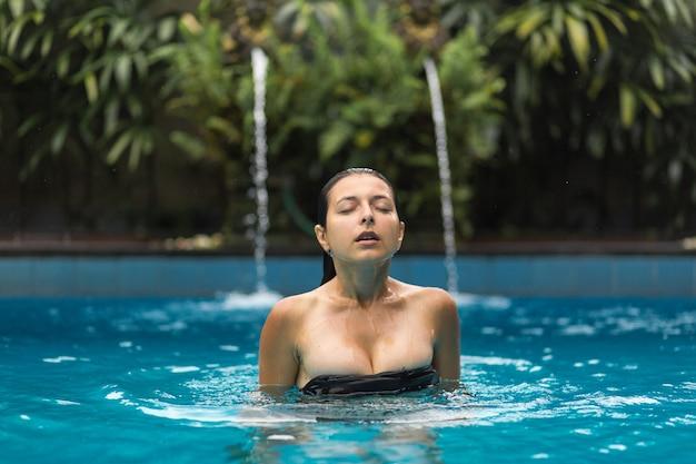 Mokra seksowna blackhair kobieta w swimsuit pozuje przy basenem.