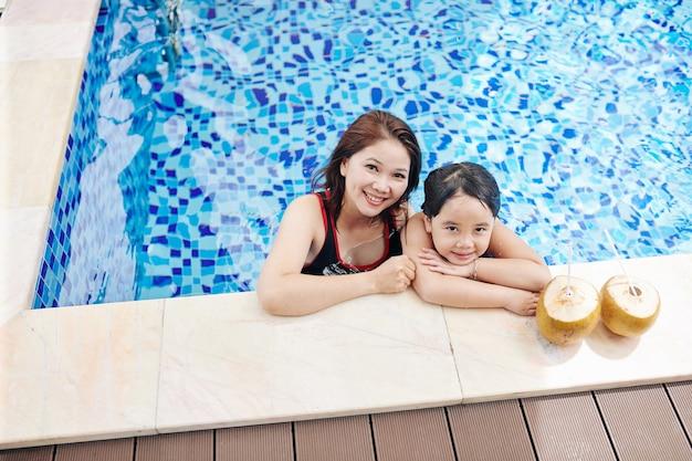 Mokra, zmęczona azjatycka matka i córka odpoczywają na brzegu basenu z kokosowymi koktajlami i patrzą w kamerę
