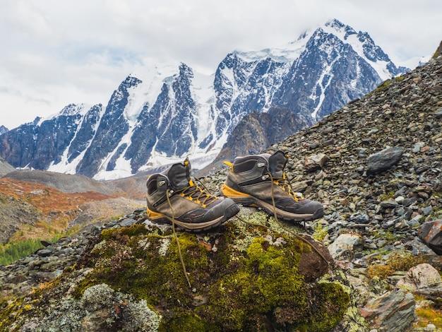 Mokre buty trekkingowe wysychają na kamieniu na tle pokrytych śniegiem wysokich gór. trudności wędrówek, suszenie ubrań na łonie natury.