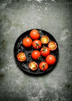 Mokre czerwone pomidory na kamiennym stole.