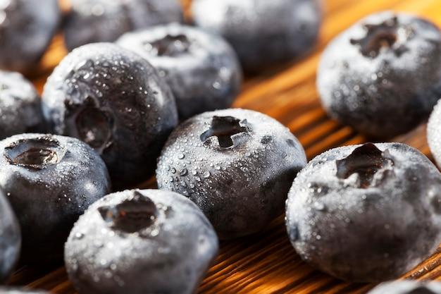 Mokre, dojrzałe, soczyste i smaczne jagody na drewnianym stole jagody są pokryte