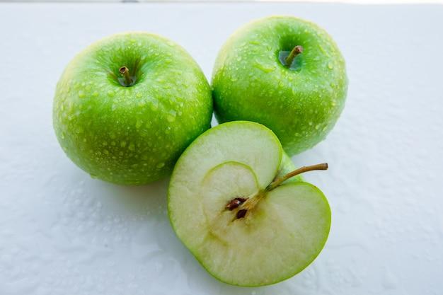 Mokre zielone jabłka i połowa na białym. zbliżenie.