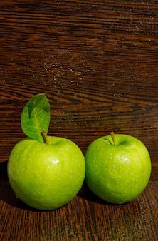 Mokre zielone jabłka z liściem na zakrzywionym ciemnym drewnie. widok z boku.