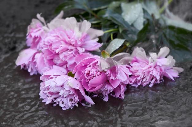 Mokry bukiet kwiatów leży w błocie po ulewnym deszczu