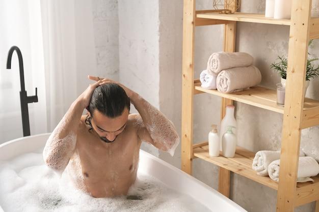 Mokry, muskularny mężczyzna myje włosy podczas kąpieli w pianie przy półkach z przedmiotami miłości własnej
