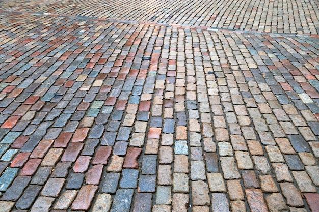 Mokry żwir na ziemi. mokra droga z kamieni. naturalny granit brukowy na drodze.