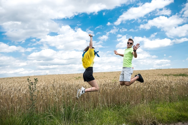 Molda szczęśliwa para z flagą ukrainy w polu pszenicy. styl życia