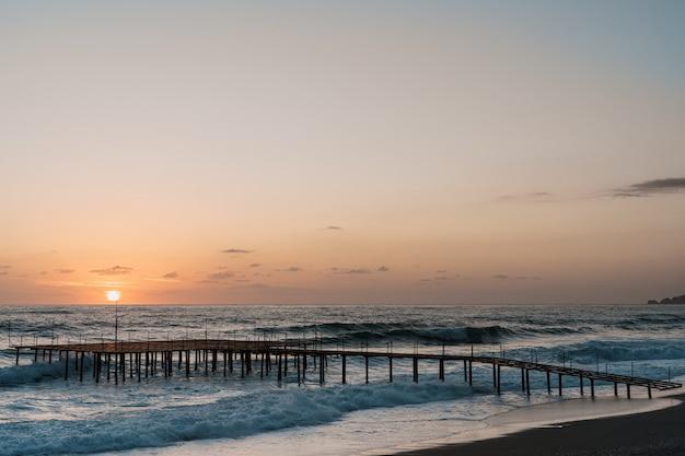 Molo na morzu w wschodzie słońca