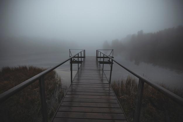 Molo nad jeziorem mglisty poranek z mistyczną mgłą jesienią