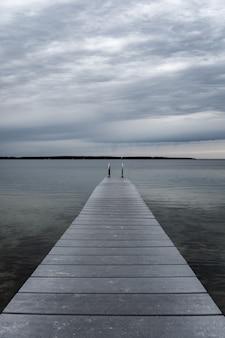 Molo nad jeziorem przeciw chmurnemu niebu