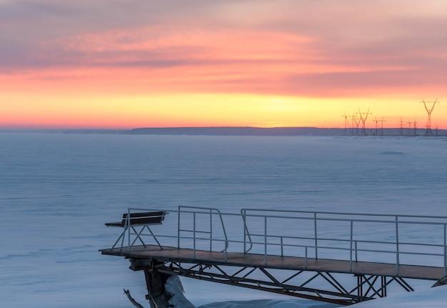 Molo przy zamarzniętym zbiorniku o zachodzie słońca zimowy wieczór złote niebo o zachodzie słońca śnieżna równina