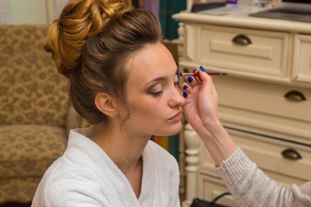 Molodoaj piękna dziewczyna robi makijaż ślubny w domu