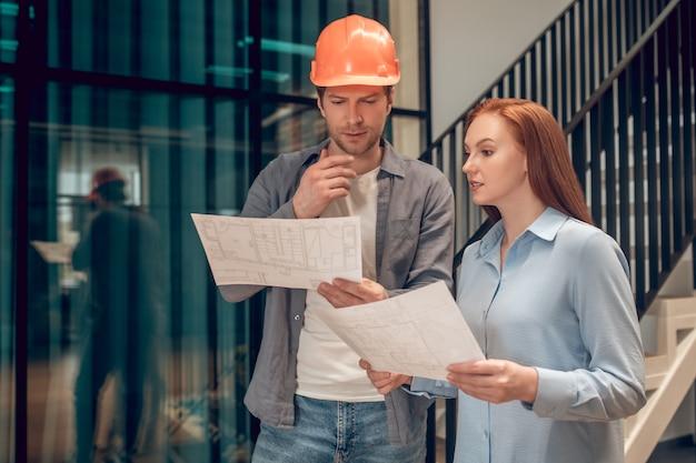 Moment pracy. mężczyzna w kasku ochronnym i długowłosa piękna kobieta stojąca w pomieszczeniu, omawiająca plan budowy, trzymająca szkice w dłoniach