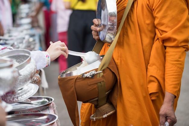 Mon ludzie oferują ryż mnichowi buddyjskiemu jałmużnę przy rankiem w wiosce, sangkhla buri, kanchanaburi, tajlandia. styl życia religii wiejskiej wczesnym rankiem.