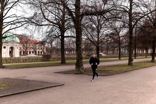 Monachium / niemcy - styczeń 2020: młody człowiek biegnący w hofgarten monachium. fitness na świeżym powietrzu w ciepły zimowy dzień. zdrowy tryb życia.