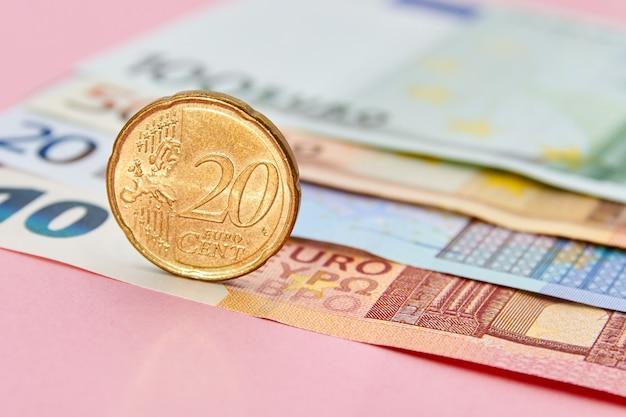 Moneta 20 centów na tle banknotów euro