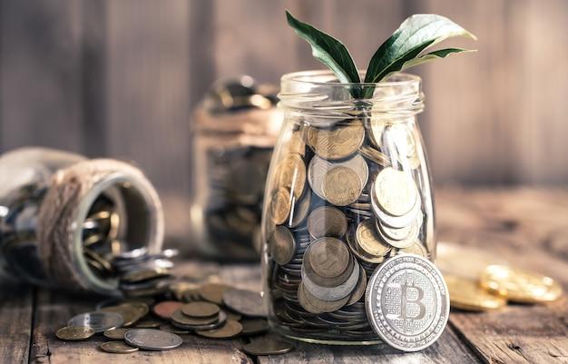 Moneta bitcoin i słoik z monetami