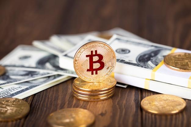 Moneta bitcoin kryptowaluty. złote monety i paczki po stu dolarowych banknotach.
